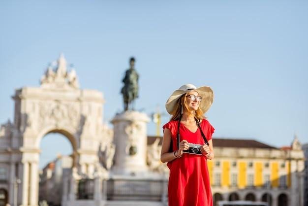 Lifestyle-porträt einer jungen frau, die während des morgenlichts in lissabon, portugal, auf dem hauptplatz mit statue und triumphbogen auf dem hintergrund spaziert