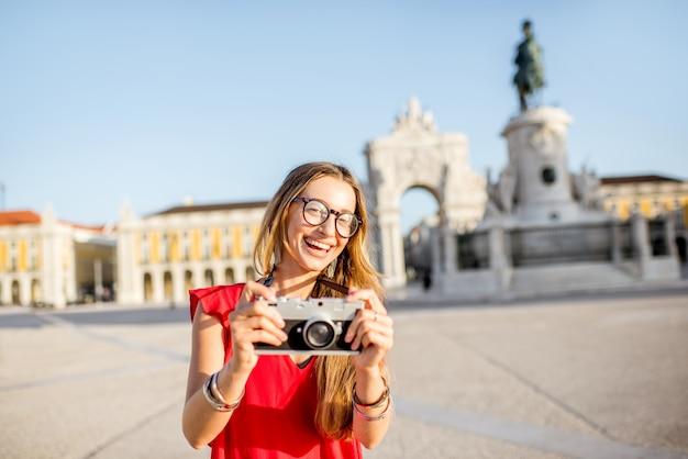 Lifestyle-porträt einer jungen touristin, die auf dem hauptplatz mit statue und triumphbogen im hintergrund während des morgenlichts in lissabon, portugal, steht
