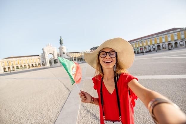 Lifestyle-porträt einer jungen touristin, die ein selfie-foto mit portugiesischer flagge auf dem hauptplatz während des morgenlichts in lissabon, portugal, macht