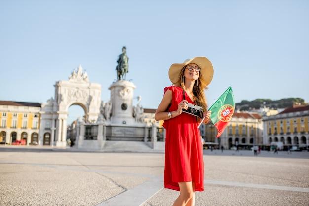 Lifestyle-porträt einer jungen touristin mit portugiesischer flagge auf dem hauptplatz während des morgenlichts in lissabon, portugal