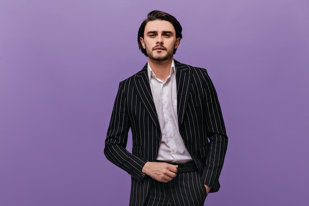 Lifestyle-porträt eines hübschen jungen mannes mit brünetten haaren, bart und schnurrbart, hellem hemd, stylischem anzug mit blick nach vorne und posiert gegen violette wand