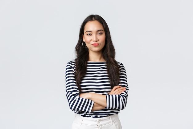 Lifestyle, schönheit und mode, menschen emotionen konzept. skeptische und verurteilende asiatische büroleiterin sieht wählerisch aus, grinst und schmollend unzufrieden, kreuzt die arme der brust