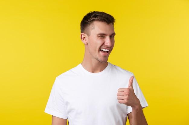 Lifestyle, sommer und menschen emotionen konzept. frecher, gutaussehender, glücklicher mann in weißem t-shirt, augenzwinkern und daumen hoch, gute arbeit loben, gut gemacht, zum erfolg gratulieren.