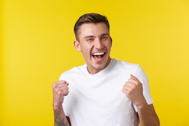 Lifestyle, sommer und menschen emotionen konzept. nahaufnahmeporträt eines fröhlichen, gutaussehenden, glücklichen kerls, der vor freude springt, lotto oder preis gewinnt, über den erfolg singt und lacht.