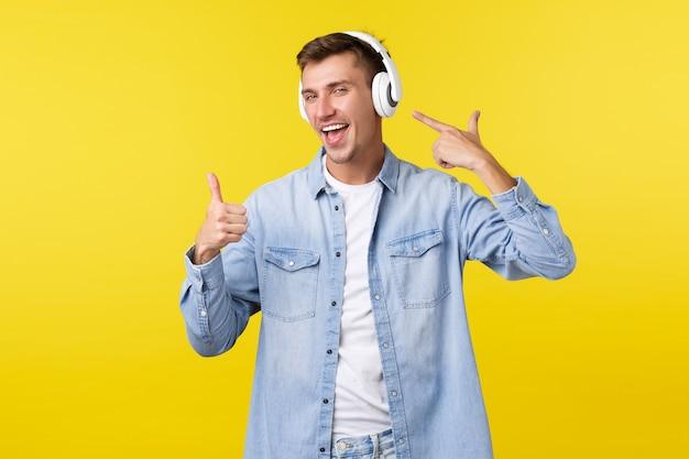 Lifestyle, sommerferien, technologiekonzept. fröhlicher gutaussehender mann, student in drahtlosen kopfhörern, der auf kopfhörer zeigt und daumen hoch zeigt, als zufrieden mit guter musik, tollen beats.