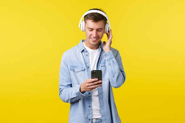 Lifestyle, sommerferien, technologiekonzept. hübscher moderner junger mann in lässigem outfit, musik in kopfhörern hören, nachrichten mit dem smartphone senden, mit dem handy eine playlist erstellen.