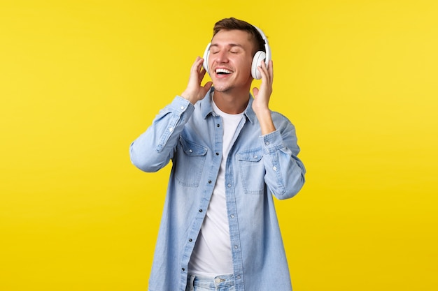 Lifestyle, sommerferien, technologiekonzept. unbeschwerter, glücklicher, gutaussehender mann, der die augen schließt und sich zufrieden fühlt, das lieblingslied in drahtlosen kopfhörern hört, sich mit dem perfekten klang zufrieden stellt.
