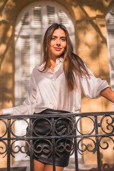 Lifestyle, süßer look einer jungen brünette in einem schwarzen lederrock und einem weißen hemd auf einem schwarzen geländer eines traditionellen hauses an einem herbstnachmittag
