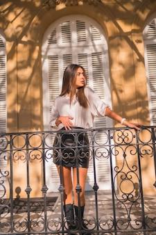Lifestyle, süßer look einer jungen brünette in einem schwarzen lederrock und einem weißen hemd auf einem schwarzen geländer eines traditionellen hauses