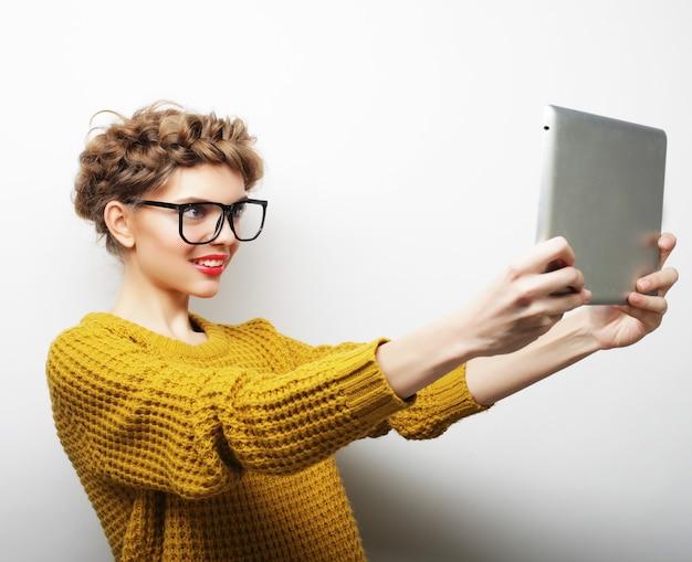 Lifestyle- und people-konzept: glückliche frau, die selfie mit digitalem tablet macht