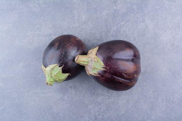 Lila auberginen isoliert auf blauer oberfläche