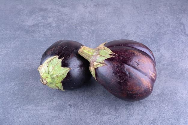 Lila auberginen lokalisiert auf betonhintergrund.