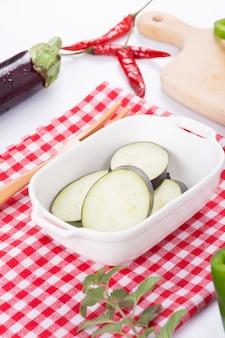 Lila auberginenscheiben in weißer schüssel