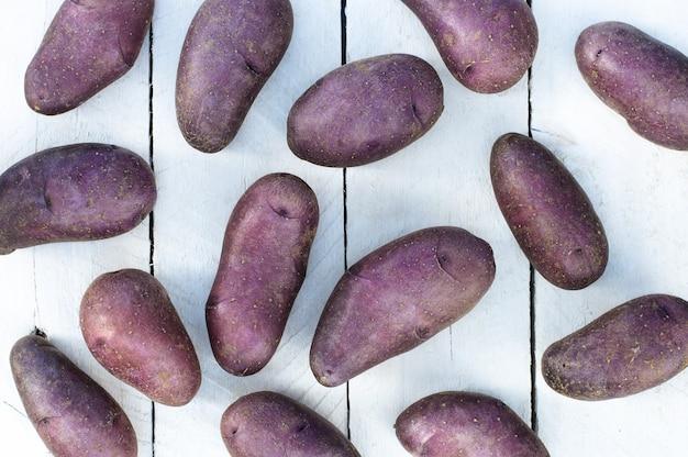 Lila bio-kartoffeln auf weißem holztisch
