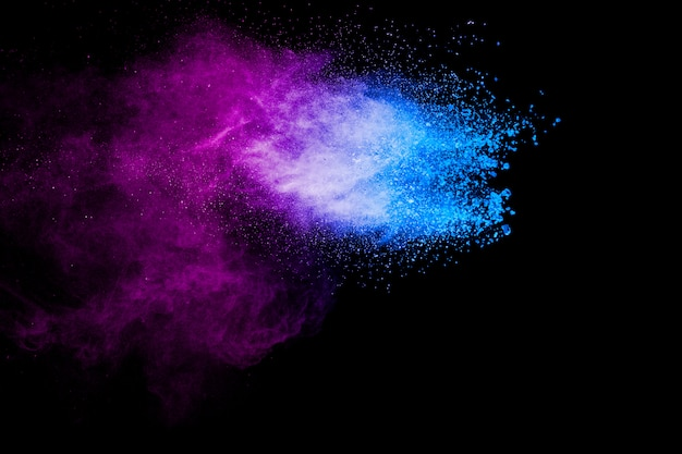 Lila blaue farbe pulver explosion wolke auf schwarzem hintergrund. nahaufnahme von lila blauen staubpartikeln spritzen.