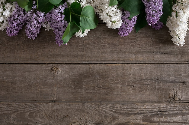 Lila blüte auf rustikalem holzhintergrund mit leerem raum für die draufsicht der begrüßungsnachricht
