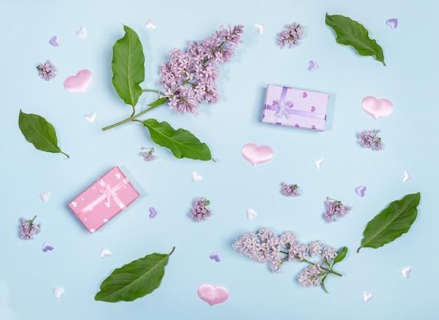 Lila blüten und blätter mit geschenkboxen auf blauem hintergrund
