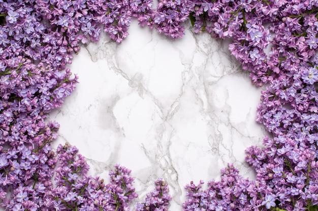 Lila blumen auf marmorhintergrund mit copyspace sommerfarb- und -feiertagskonzept.