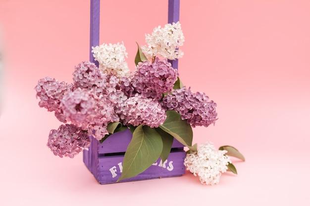 Lila blumen bündeln in einem violetten hölzernen korb über rosa hintergrund. schönes violettes lila blumenstillleben ostern-grenzdesign auf holztisch