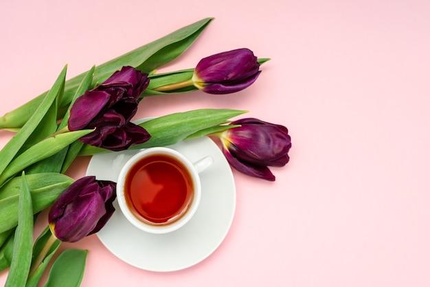Lila blumen und eine weiße kaffeetasse auf einem rosa hintergrund. ein schönes banner mit platz zum kopieren.