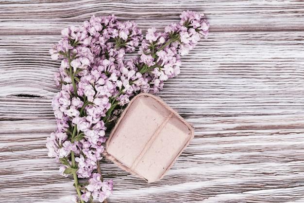 Lila blumen und kleine geschenkbox aus papier mit überraschung