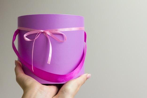 Lila box mit rosa box in der hand der frau