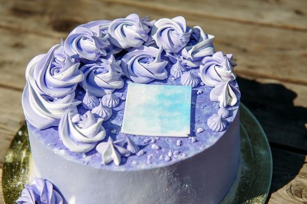 Lila geburtstagstorte mit cremefarbenen blumen, nahaufnahme. hochzeitssüßigkeiten, blaubeerkuchen verziert mit dekorativem aufkleber, draufsicht