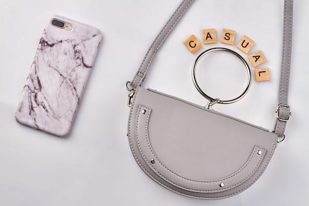 Lila geldbörse und handy auf weißem hintergrund. marmor handyhülle und schöne freizeittasche.