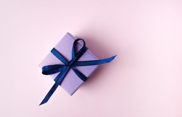Lila geschenk mit blauem band auf hellblauem hintergrund. kopierraum
