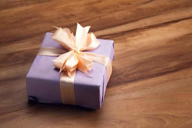 Lila geschenkbox auf dem holztisch