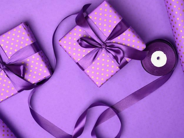 Lila geschenkbox in seidenband gewickelt auf lila hintergrund, ansicht von oben