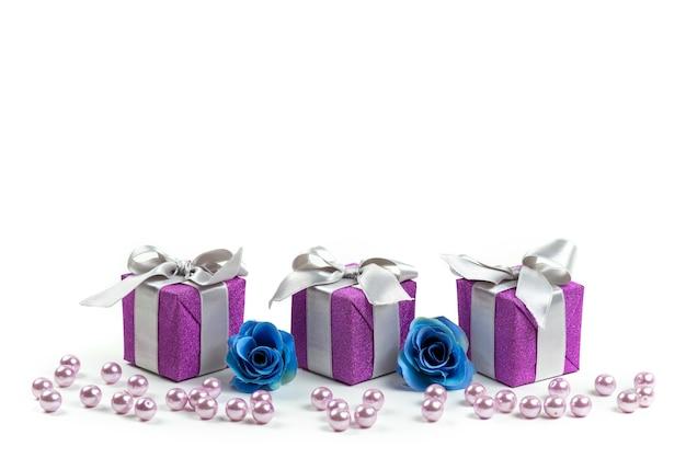 Lila geschenkboxen der vorderansicht mit grauen schleifen auf weißem schreibtisch