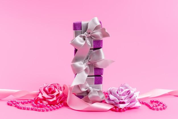 Lila geschenkboxen der vorderansicht mit schleifen und blumen auf rosa schreibtisch