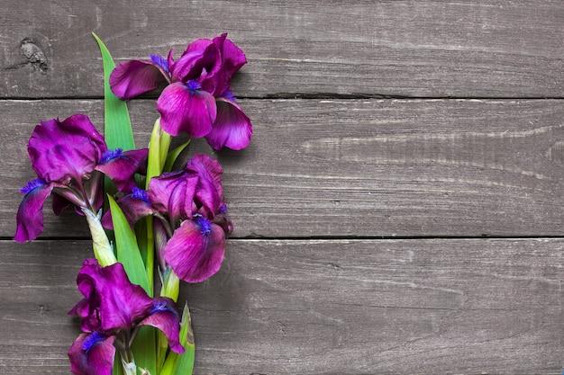 Lila irisblumenstrauß auf rustikalem hölzernem hintergrund. flach liegen. draufsicht mit kopierraum