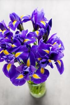 Lila irisblumenvase, auf dem hintergrund.
