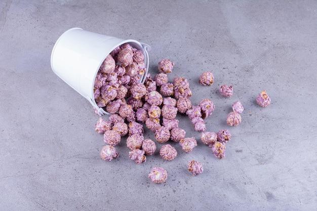 Lila kandiertes popcorn, das aus einem eimer auf marmorhintergrund gießt. foto in hoher qualität
