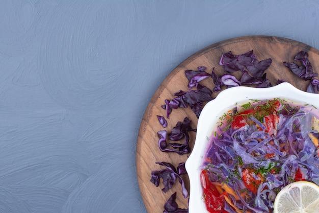 Lila kohlsuppe mit chilischoten auf einem holzbrett