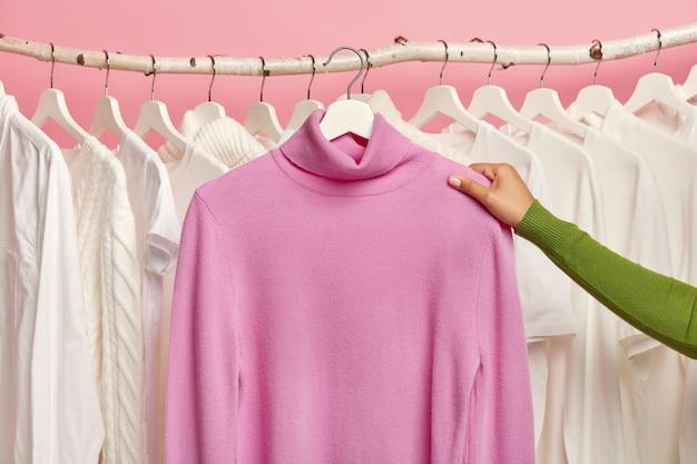 Lila lässiger pullover auf kleiderbügeln in der hand der frau gegen schiene mit schneeweißer kleidung.