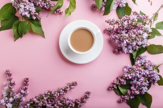 Lila lila blumen und eine tasse kaffee auf pastellrosa.