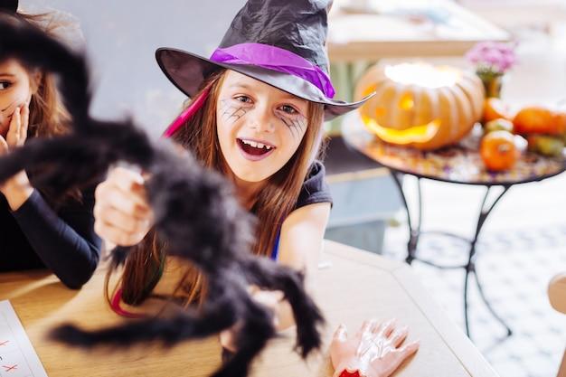 Lila lippen. strahlendes dunkelhaariges mädchen mit lila lippen, die zauberer-halloween-kostüm tragen, während party besuchen