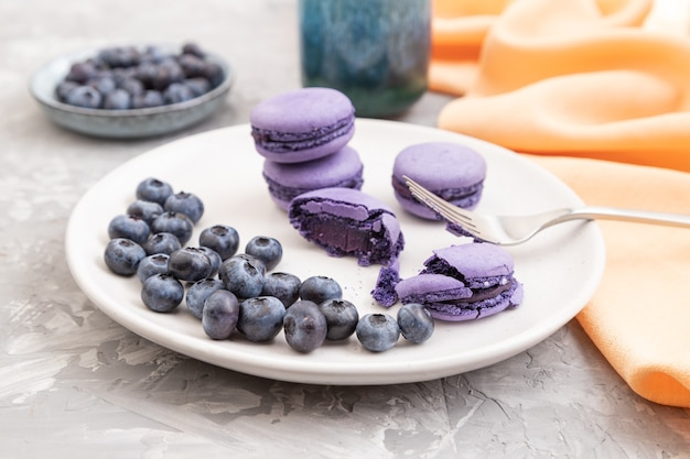 Lila macarons oder macarons-kuchen mit blaubeeren auf weißer keramikplatte auf grauer betonoberfläche und orangefarbenem textil
