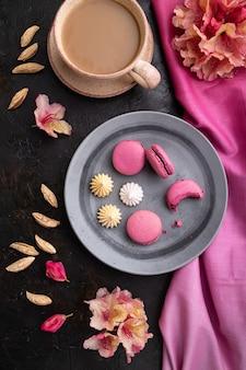 Lila macarons oder macaroons kuchen mit tasse kaffee auf einem schwarzen betonhintergrund und rosa textil. draufsicht, flach liegen,