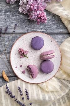 Lila macarons oder macaroons-kuchen mit tasse kaffee auf grauem hölzernem hintergrund und weißem leinentextil. draufsicht, flach liegen,