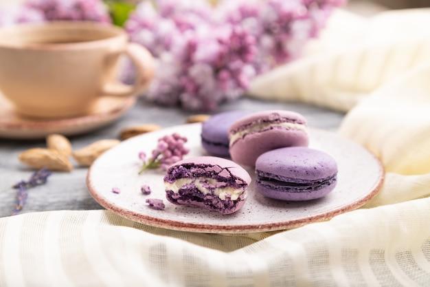 Lila macarons oder macaroons-kuchen mit tasse kaffee auf grauem hölzernem hintergrund und weißem leinentextil. seitenansicht, nahaufnahme,