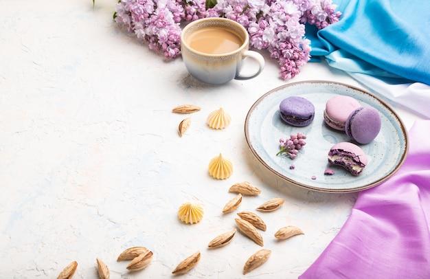 Lila makronen oder makronen backen mit tasse kaffee auf weißem betonhintergrund und magentablem textil zusammen. seitenansicht,