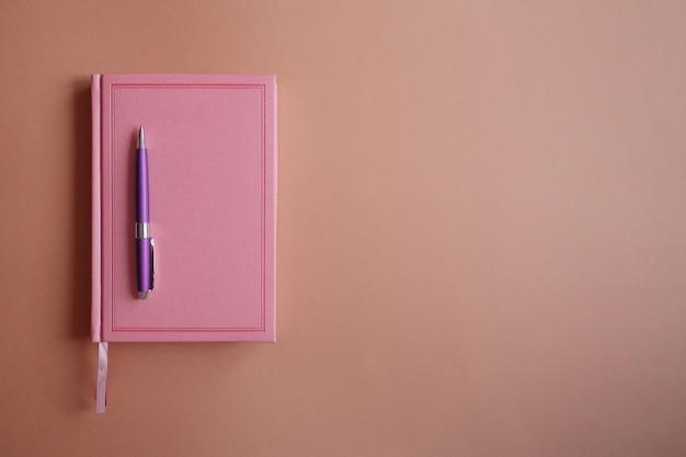 Lila metallstift auf rosa notizbuch oder tagebuch, auf rosa papier