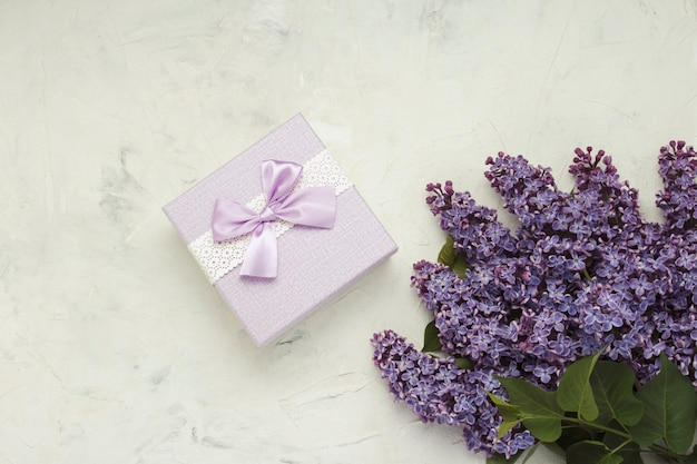Lila niederlassungen, geschenkbox auf einer hellen steinoberfläche. konzept des frühlings. flachgelegt, draufsicht