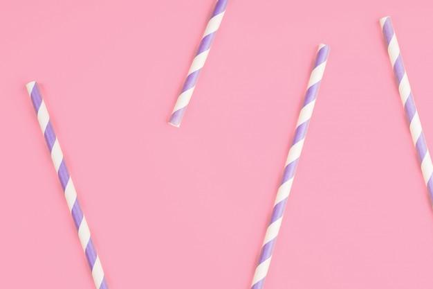 Lila papierstrohe auf rosa