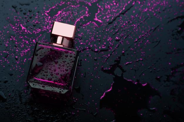 Lila parfüm auf schwarzem hintergrund