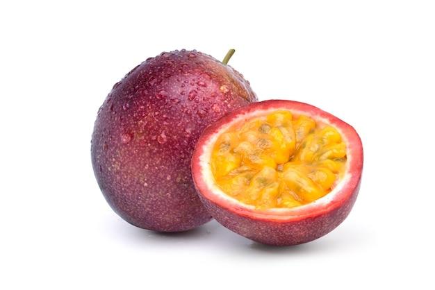 Lila passionsfrucht mit halbiertem schnitt und wassertropfen isoliert auf weiß